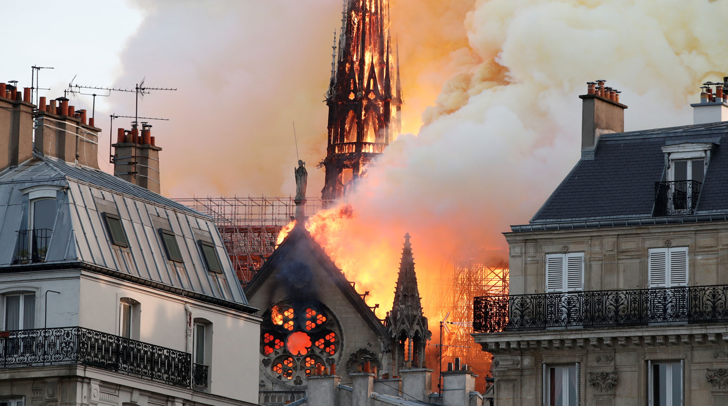 Smoke billows as fire engulfs the spire of Notre Dame Cathedral in Paris, France April 15, 2019. REUTERS/Benoit Tessier - RC19CF540000