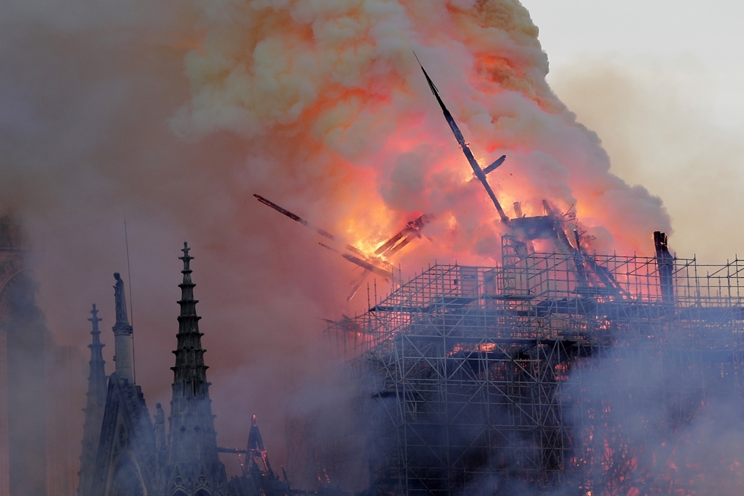 epa07508763 The spire collapses while flames are burning the roof of the Notre-Dame Cathedral in Paris, France, 15 April 2019. A fire started in the late afternoon in one of the most visited monuments of the French capital. EPA-EFE/IAN LANGSDON